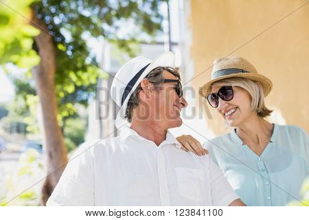 Smiling couple looking eachother in city