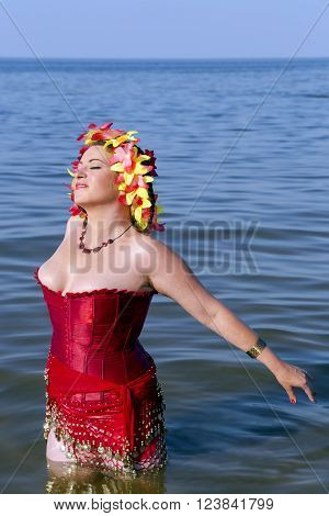 Beautiful woman in a red corset and floral chaplet in the Baltic sea, Jurmala, Latvia