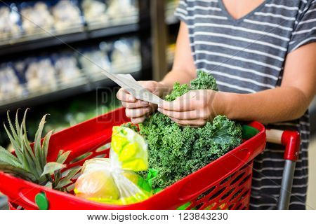 Woman with red basket holding list in supermarket