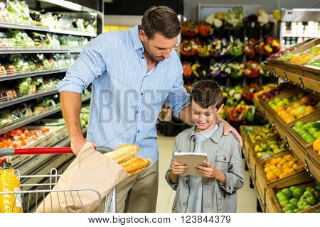 Father and son reading the grocery list in the supermarket