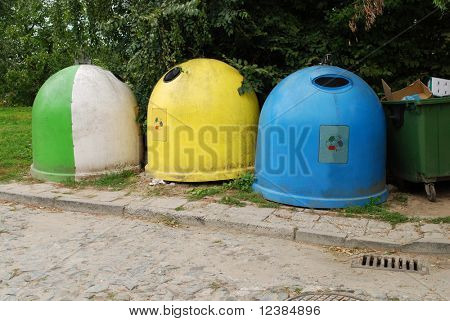 Three colorful recycling bins in a city center. Glass, plastic, paper.