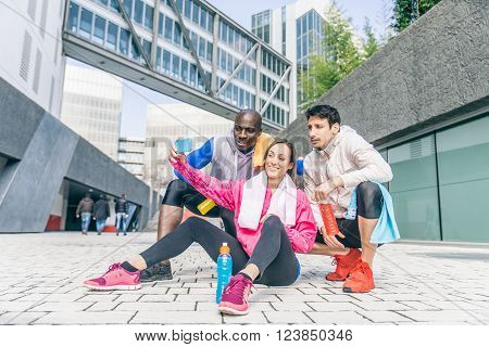 Multi-ethnic friends taking a selfie after a run in a urban area - Three runners resting after a workout session