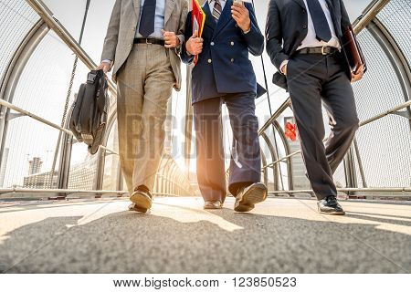 Three businessmen walking in a financial area while having a conversation - Work colleagues going to work