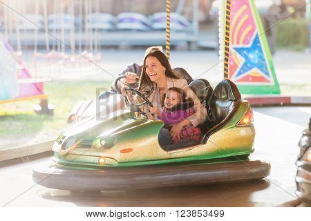 Cute little girl with her mother having fun at fun fair, driving a bumper car, amusement park