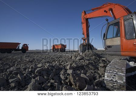 Crawler excavator loads the soil dump trucks