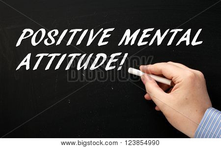 Hand writing the words Positive Mental Attitude in white text on a blackboard as a reminder of one of the attributes to look for in people