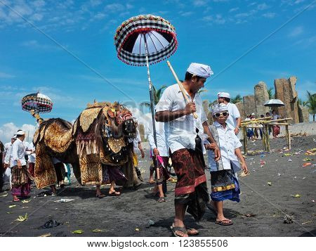 BALI INDONESIA - March 6 2016: A Balinese father walks with his young son as sacred temple effigies are carried along the beach during a Hindu religious ceremony on March 6 2016 in Bali Indonesia.