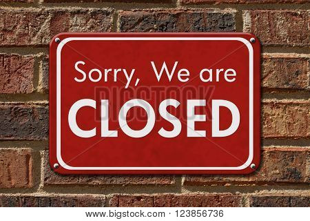 Sorry We are Closed Sign A red hanging sign with text Sorry We are Closed on a brick wall