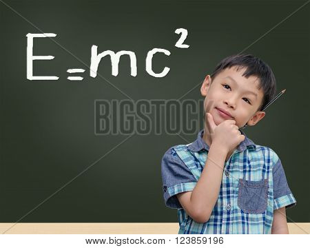 Young Asian boy thinking in front of chalkboard