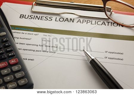 pen,small business load application on clip board.Clip board ,glasses, on wood table.