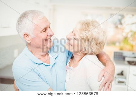 Happy senior couple smiling while looking at eachother at home