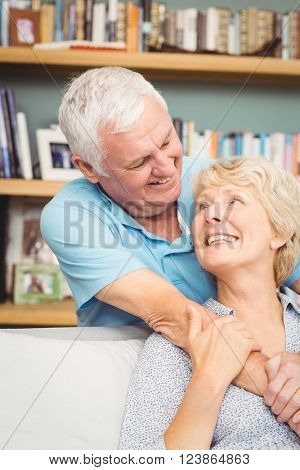 Happy senior couple hugging against bookshelf at home