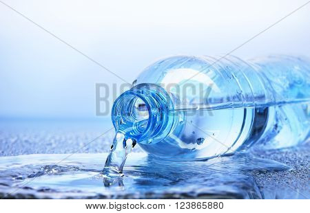 Water Pouring From Plastic Bottle With Reflection