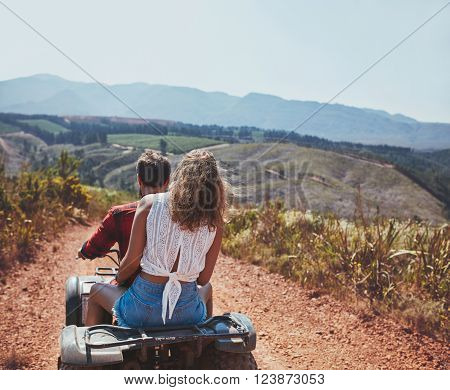 Rear view shot of young couple riding on a quad bike in countryside. Woman behind her boyfriend driving an ATV on country road on a summer day.