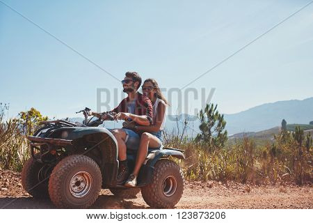 Young man and woman riding on a quad bike. Couple on holiday enjoying on a ATV bike ride on a summer day.