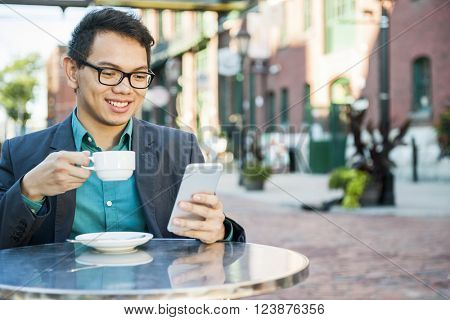 Young asian man in business casual attire sitting and smiling in relaxing outdoor cafe drinking cup of coffee while using mobile phone, copy space.
