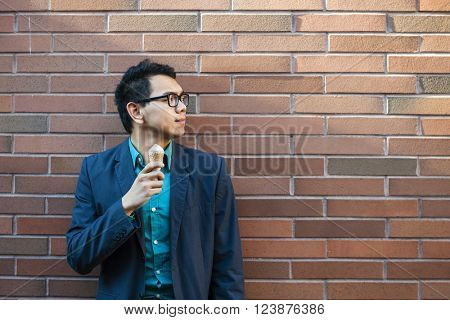 Young asian man in his twenties with ice cream while standing alone near brick wall outside looking to the side