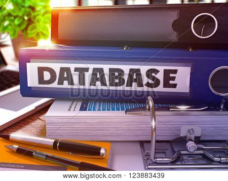Blue Ring Binder with Inscription Database on Background of Working Table with Office Supplies and Laptop. Database - Toned Illustration. Database Business Concept on Blurred Background. 3D Render.