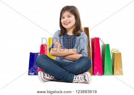 Happy young and beautiful shopping girl sitting isolated on white studio background