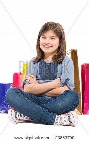 Young and beautiful shopping girl sitting with shopping bags on white background