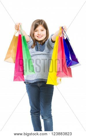 Young and adorable shopping girl offering presents or gifts on white background