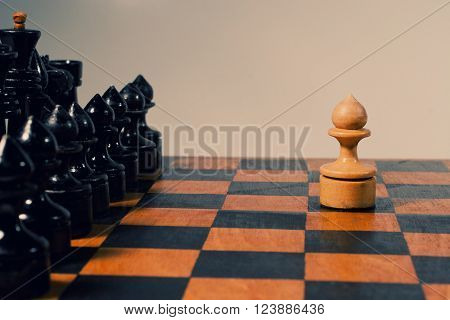 Single white pawn and rows of black chess figures on an old chessboard (retro style)