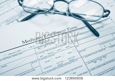 A medicare enrollment paper form and glasses ** Note: Shallow depth of field