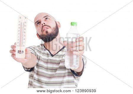 Heat wave in summer season concept with man holding thermometer and cold water bottle