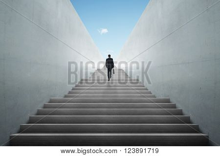 Ambitions concept with business man climbing stairs