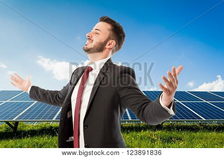 Happy smiling businessman with wide outspread or outstretched arms on solarpower photovoltaic panel background