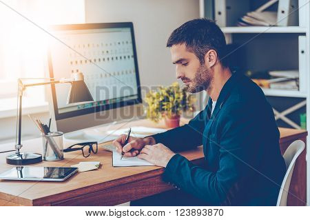 Working moments. Side view of confident young man writing something in his notebook while sitting at his working place in office