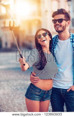 Joyful selfie. Joyful young loving couple making selfie on smart phone while standing outdoors
