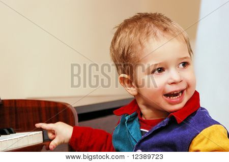 kid playing piano and lauphing