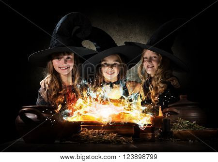 Three little Halloween witches reading conjure from magic book above pot