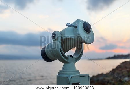 Public monocular on sea shore. Coin operated binocular viewer on blurred background of sunset and sea. Shallow depth of field. Selective focus.