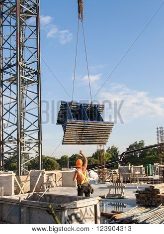 Construction worker receiving a stack of scaffolding pieces from a crane on a construction site
