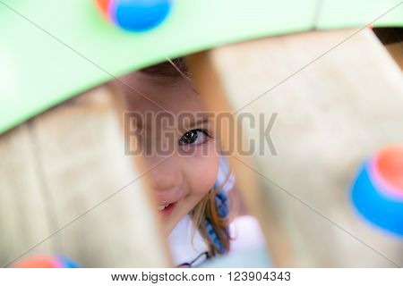 Little girl playing hide and seek in a playground.