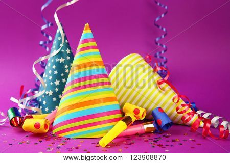 Three Birthday hats with serpentine streamer and noise makers on purple background