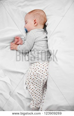 Loving baby with dummy sleeping on soft bed, close up