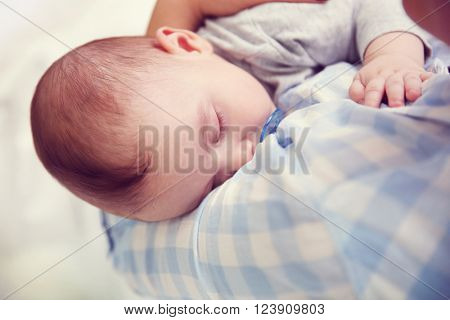 Loving baby with dummy sleeping in mother's hands, close up
