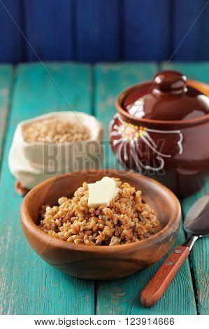 Wholegrain spelt porridge with butter in wooden bowl and raw spelt in linen bag on wooden table vertical