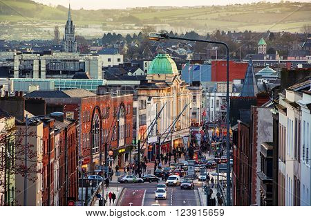 Cork Ireland city center with various shops bars and restaurants. Car traffic and people at the street. Mountains at the background