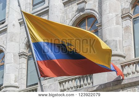 Low angle view of big ecuador flag flying against classical style building at the historic center of Quito Ecuador.