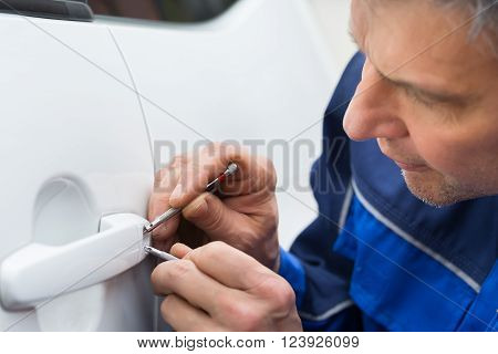 Hand Holding Lockpicker To Open Car Door