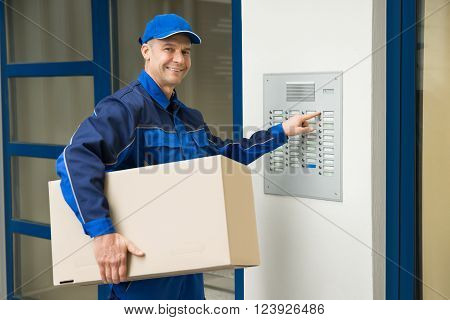 Delivery Man Pressing Button Of Intercom To Enter Building