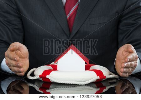 Businessman Hand Protecting House Model With Lifebelt