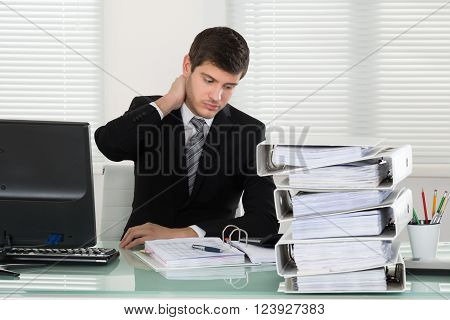 Businessman Suffering From Neckache With Invoice On Desk