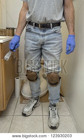 Body shot of plumber wearing kneepads installing a new toilet