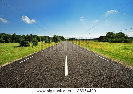 Rural highway on a clear sunny summer day. Black asphalt brand new road.