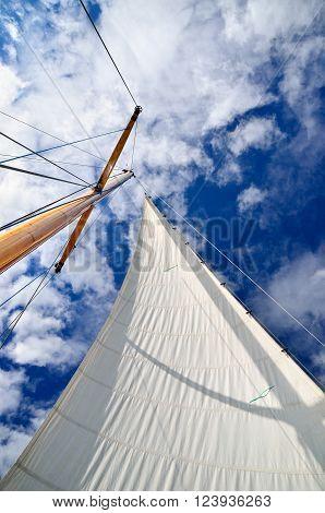Sail yacht mast with white sail against dark blue sky